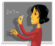 Teacher writing on chalkboard Royalty Free Stock Photos