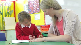 Teacher Writing With Female Pupil At Desk stock video footage
