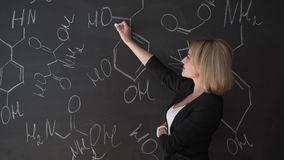 Teacher writing formulas on the chalk Board and explains the students the formula. Teacher writing formulas on the chalk Board and explains the students the stock video