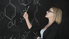 Teacher writing formulas on the chalk Board and explains the students the formula. Teacher writing formulas on the chalk Board and explains the students the stock video footage