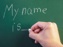 Teacher writing on green chalkboard. My name is with white chalk Stock Photos