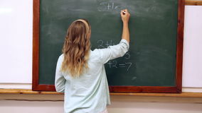 Teacher writing mathematics on board. At the elementary school stock video