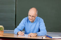 Teacher writing notes at his desk. Mature male teacher sitting writing notes at his desk in front of the chalkboard Stock Photos