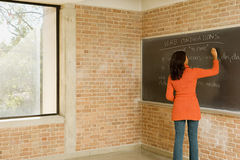 Teacher writing Spanish text on blackboard royalty free stock photography