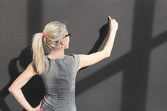Teacher writing with white chalk on empty blackboard in classroom Royalty Free Stock Images