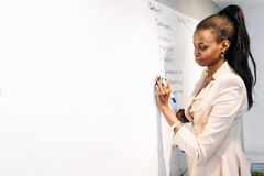 Teacher  writing on whiteboard. And being instructive Stock Images