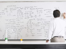 Teacher Writing On Whiteboard. Rear view of teacher writing on whiteboard Stock Photography