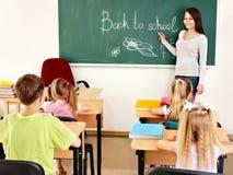Teacher writting at blackboard in classroom Royalty Free Stock Photos