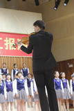 Teacher xuxin play the violin and conduct. Teacher xuxin is well-known violinist. while play the violin, while conduct. this is the  famous chinese children's Royalty Free Stock Photography