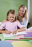 Teacher and young student in class writing Royalty Free Stock Photo