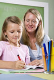 Teacher and young student in class writing Stock Image