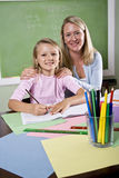 Teacher and young student in class writing Stock Photo