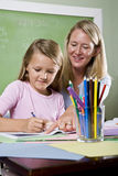 Teacher and young student in class writing Royalty Free Stock Image
