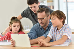 Teacher with young students using tablet Royalty Free Stock Photography