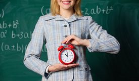 Teachers attributes. Alarm clock in hands of teacher or educator classroom chalkboard background. School discipline. Concept. Schedule and regime. Alarm clock royalty free stock photography