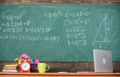 Teachers attributes. Table with school supplies alarm clock books and mug classroom chalkboard background. Working stock photo