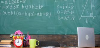 Teachers attributes. Working conditions which prospective teachers must consider. Traditional teachers workplace. Table. With school supplies alarm clock books stock photography