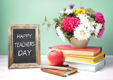 Teachers day concept image. Techers day concept.Knowledge day.Flowers,stack of books,apple on table empty copy space royalty free stock photos