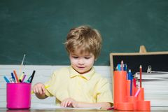 Teachers day - education for pupil in school. Happy cute industrious child is sitting at a desk indoors. royalty free stock images