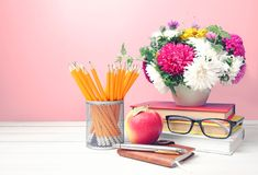 Teachers day,empty copy space background. Teachers day,flowers pencils stack of books and apple on table empty space background stock photo