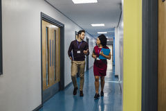 Teachers In The Hall. Two teachers are talking in the school hall as they walk to their next lesson together royalty free stock photos