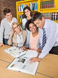 Teachers And Students Discussing Over Book In Stock Images