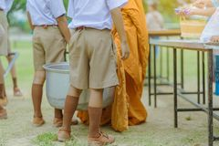 Teachers and students together make merit to give food offerings to a Buddhist monk on important religious days. At school stock photography