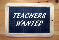Teachers Wanted. The phrase Teachers Wanted in white text on a slate blackboard placed on a wooden background royalty free stock photos