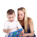 Teaching. Beautiful blonde girl teaching her little brother stock image