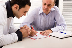Teaching. Older instructor teaches young man stock image