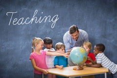 Teaching against blue chalkboard. The word teaching and cute pupils and teacher looking at globe in library against blue chalkboard Stock Photography