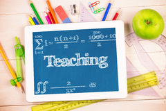 Teaching against students desk with tablet pc. The word teaching and maths equation against students desk with tablet pc Royalty Free Stock Images