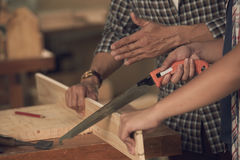 Teaching apprentice. Close-up image of carpenter explaining his apprentice how to saw wood Stock Photography