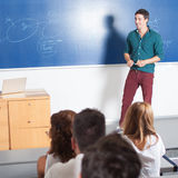 Teaching Asisstent. Young professor giving class in lecture hall Stock Image