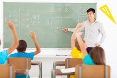 Teaching chinese language. Smiling educator teaching chinese language to group of primary kids Royalty Free Stock Photo