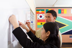 Teaching chinese writing. A chinese female teacher teaching chinese writing to a male adult african student in the classroom stock photography