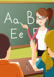 Teaching Class. Stylish young teacher in classroom, teaching young students in preschool or elementary school setting with Words on chalkboard Royalty Free Stock Image