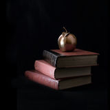 Teaching Classics. Concept image for teaching classics. Golden apple on top of antique books against a black background. Copy space royalty free stock photo