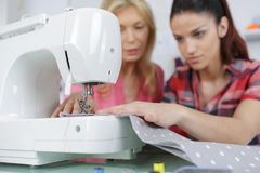 Teaching daughter to sew. Teaching the daughter to sew Royalty Free Stock Photography