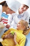 Teaching dental hygiene. Photo of dentist teaching care dental hygiene little girl with assistant near by Stock Image