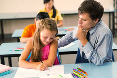 Teaching drawing. Young male teacher explaining schoolgirl how to draw an animal Stock Image