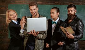 Teaching and education occupation. Diversity concept. School staff. People with laptop book stand in school classroom. School teachers. Bearded men masculine stock image