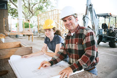 Teaching Engineering to Student. Engineer going over blueprints with a student on the construction site Stock Photography