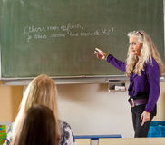 Teaching french. Teacher standing in front of the classroom teaching french stock photography