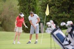 Teaching friend to play golf stock photos