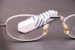 Teaching. Glasses looking at a piece of chalk as a concept for teaching, education or scrutiny thereof with copy space - focus is on the tip Royalty Free Stock Image