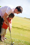 Teaching Golf. Father teaching his son to play golf stock photography