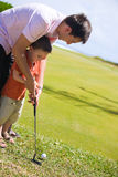 Teaching Golf. Father teaching his son how to play golf Royalty Free Stock Image