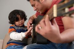 Teaching guitar. Asian men teaching his son how to play guitar Royalty Free Stock Image
