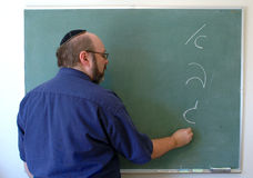 Teaching Hebrew. Jewish man writes the hebrew alphabet on a chalkboard stock photography